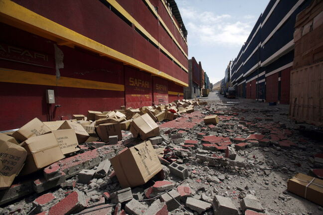 A street is covered by debris from the earthquake damaged Duty Free Zone of Iquique, in Iquique, Chile, Friday, April 4, 2014. Following a magnitude-8.2 earthquake early in the week, soldiers have kept a close watch on supermarkets and gas stations to prevent looting as many people continued to line up on Friday for gasoline, water and food. The city remained largely peaceful and no new major damage or casualties were reported from the continuing aftershocks that have rattled the sleep-deprived citizens of Chile's north.