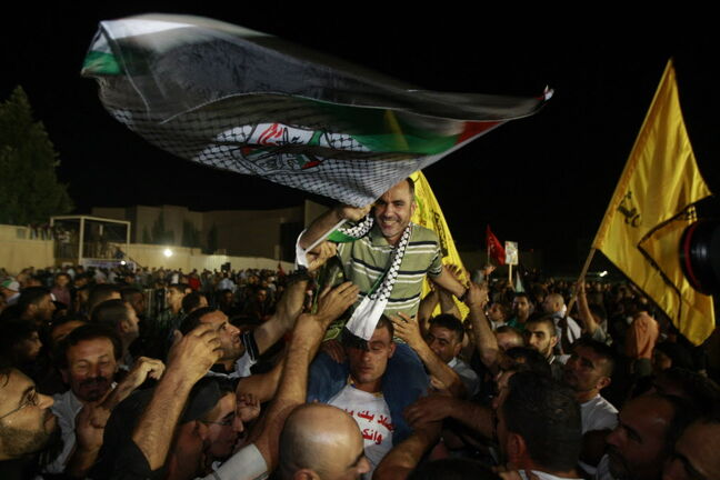 A released Palestinian prisoner Esmat Mansour, centre, waves a flag as he is cheered at the Palestinian Authority headquarters in the West Bank city of Ramallah earlier in April.