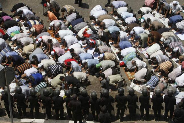 Egyptian anti-riot policemen stand guard as Muslim Brotherhood supporters pray during a demonstration outside the State Council in Cairo, ahead of an anticipated Administrative Court ruling on the dissolution of Parliament. (AP Photo/Amr Nabil)