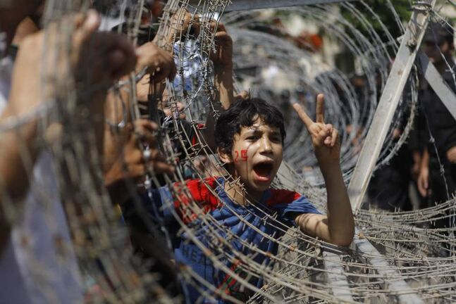 An Egyptian boy peers out of barbed wire, his face painted with the number 25, the date of the Egyptian revolution, during a protest in front of the Supreme Constitutional Court in Cairo, Egypt, Thursday June 14, 2012. Egypt's highest court has ruled that Hosni Mubarak's last prime minister can stay in the presidential race.