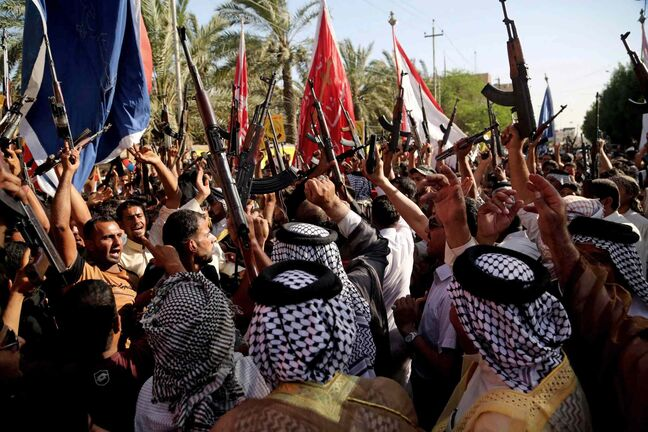 Shiite tribal fighters raise their weapons and chant slogans against the al-Qaida-inspired Islamic State of Iraq and the Levant (ISIL) in Basra, Iraq's second-largest city, southeast of Baghdad, Iraq, Monday. Sunni militants captured a key northern Iraqi town along the highway to Syria early on Monday, compounding the woes of Iraq's Shiite-led government a week after it lost a vast swath of territory to the insurgents in the country's north.