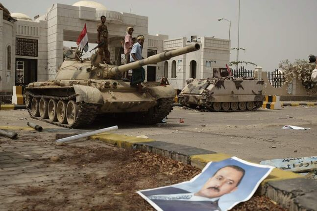 A poster of Yemen's former President Ali Abdullah Saleh lies on the ground as army soldiers and tribesmen loyal to the army gather on a tank in front of the local authority compound in the city of Zinjibar, Yemen after they retook the city from al-Qaida militants, Thursday, June 14, 2012. Airstrikes and clashes intensified in southern Yemen on Wednesday as army troops followed major victories with more pressure on al-Qaida militants holding small towns, according to tribal and military officials. The attacks came a day after Yemeni forces regained control of two major al-Qaida strongholds, Jaar and Zinjibar, which were in the hands of the militants for more than a year.