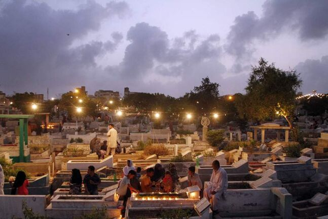 People offer prayers at graves of their relatives in a local graveyard of Karachi, Pakistan on the occasion of Shab-e-Barat. Muslims across the country observe the holy Shab-e-Barat, the night of fortune, gather at mosques offer nightlong special prayers besides visiting graves of their near and dear ones, seeking Allah's blessings for the departed souls. (AP Photo/Shakil Adil)