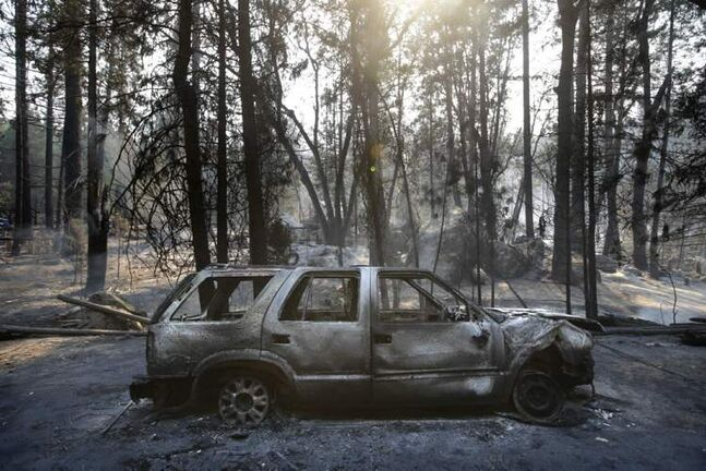 A burned SUV sits in front of a campground destroyed by the Rim Fire near Yosemite National Park, Calif., on Monday.