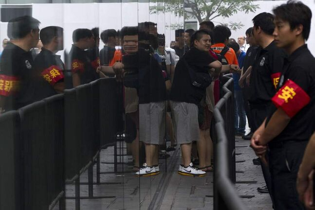 Security workers guard an entrance while customers who ordered the new iPad online wait to enter an Apple store in Beijing, China. (AP Photo/Alexander F. Yuan)