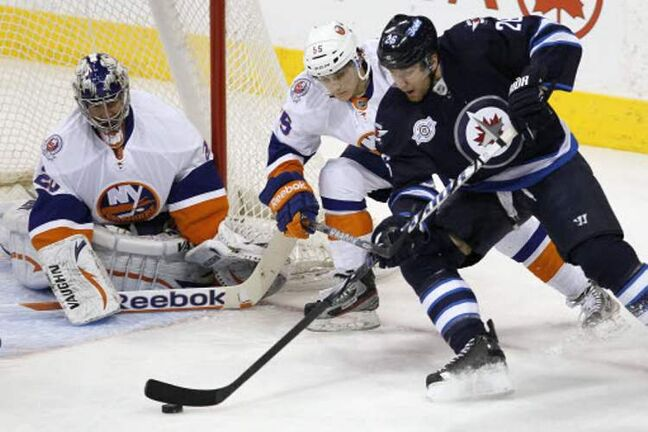The Winnipeg Jets' Blake Wheeler (26) attempts a wraparound against the New York Islanders' Aaron Ness (55) and goaltender Evgeni Nabokov (20) during first-period play at the MTS Centre on Tuesday.