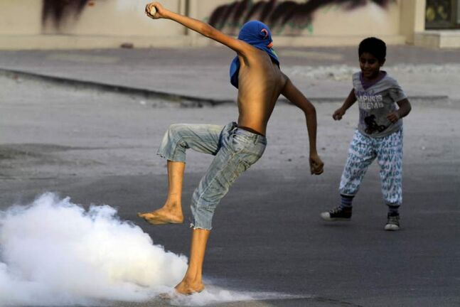 A Bahraini anti-government protester kicks away a tear gas canister fired by riot police during clashes in Saar, Bahrain, west of the capital Manama. (AP Photo/Hasan Jamali)