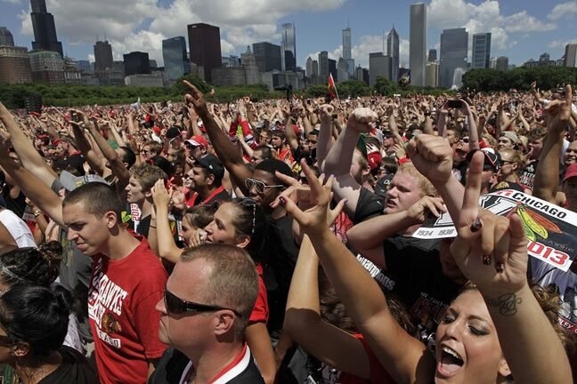 Fans cheer in Grant Park for a rally to honor the Stanley Cup hockey champions Friday, June 28, 2013, in Chicago. (AP Photo/Kiichiro Sato)