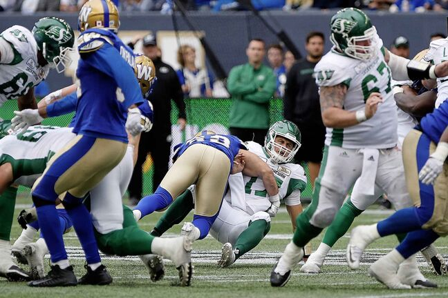 Saskatchewan Roughriders quarterback Zach Collaros (17) gets hit by Winnipeg Blue Bombers' Jeff Hecht (29) during second half CFL action in the 15th annual Banjo Bowl in Winnipeg Saturday, September 8, 2018. THE CANADIAN PRESS/John Woods