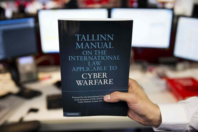 A copy of the Tallinn Manual, a rulebook on cyberwarfare, is held up in a posed photograph in London, Tuesday, March 19, 2013. Even cyberwar has rules, and one group of experts is publishing a manual to prove it.