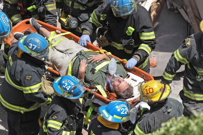 Philadelphia firefighters carry a survivor from the rubble of the building.