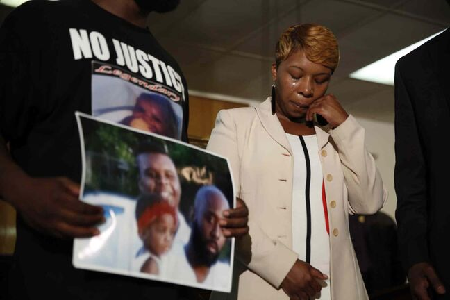 Lesley McSpadden, the mother of 18-year-old Michael Brown, wipes away tears as Brown's father, Michael Brown Sr., holds up a family picture of himself, his son, top left, and a young child during a news conference Monday, Aug. 11, 2014, in Jennings, Mo.