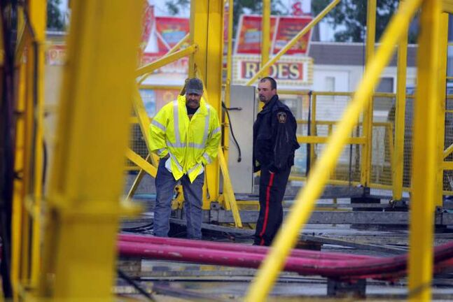 A Red River Ex worker and police officer look at the Crazy Mouse ride following an accident involving a boy Thursday.