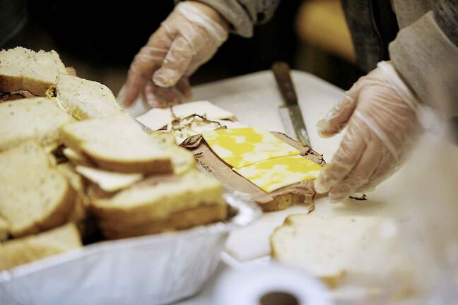 JOHN WOODS / WINNIPEG FREE PRESS Volunteers make sandwiches at the Love Lives Here drop-in at Austin Street and Henry Avenue in downtown Winnipeg. The Christian mission supports about 100 people several times a week.