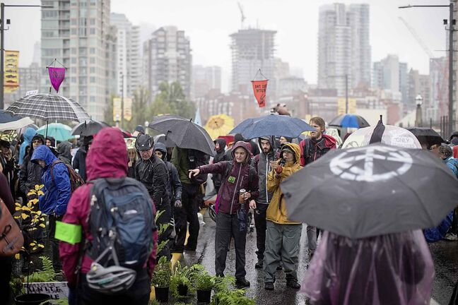 Protesters with the group Extinction Rebellion occupy the Burrard Street Bridge in Vancouver, closing it to vehicle traffic going into and out of downtown. (Darryl Dyck / The Canadian Press)