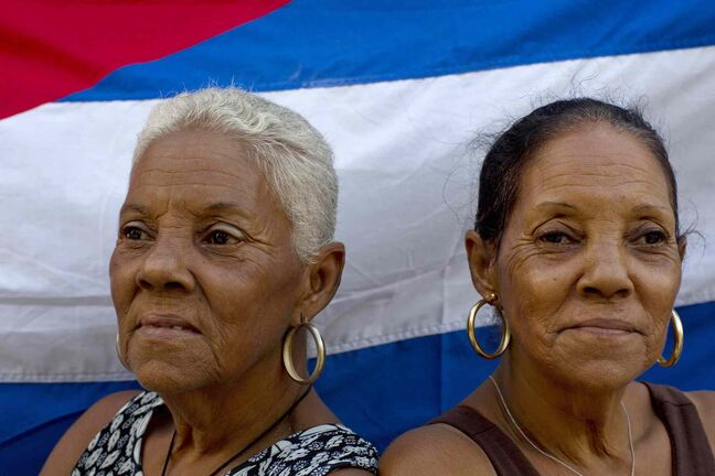 Sixty-five-year-old Fe Fernandez, left, and her sister Esperanza pose for a portrait in front a Cuban flag on their street in Havana, Cuba.