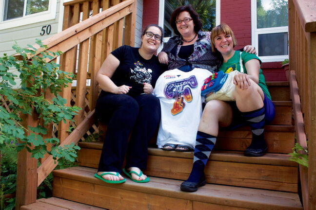 Winnipeg Fringe Festival performers Brie Watson (left) and Erin Rodgers (right) of Toronto flank billet host Heather Madill in front of Madill's Elmwood home. The Toronto duo put on the sketch comedy production Water Wings during the festival.