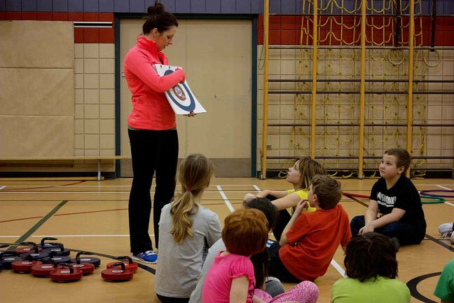Kerri Einarson second Liz Fyfe shows a Grade 4 class at Prince Edward School the basics of curling.
