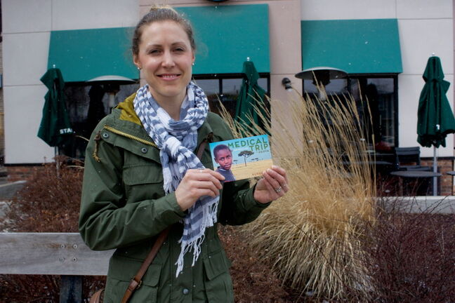 Adrienne Pearson holds a postcard detailing the medical trip she and 10 others will take to Kenya this summer.
