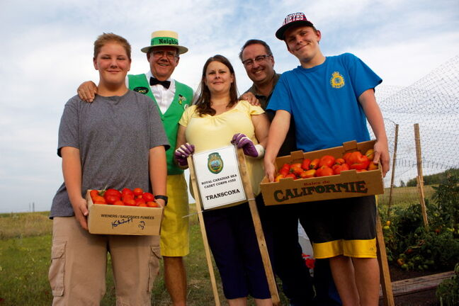 From left to right, Evan Evaniuk, Hi Neighbour Sam (Peter Martin), Lt. Shari Howells, Lt. Mike Gnutel, and Riley Howells are shown with the tomatoes the RCSCC #350 Transcona Sea Cadets grew for Winnipeg Harvest.