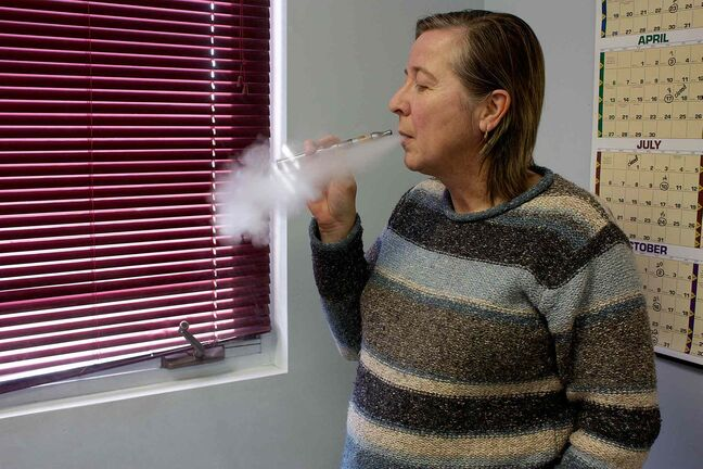 E-cigarette user Kathy Martin is shown exhaling vapour from her e-cigarette.
