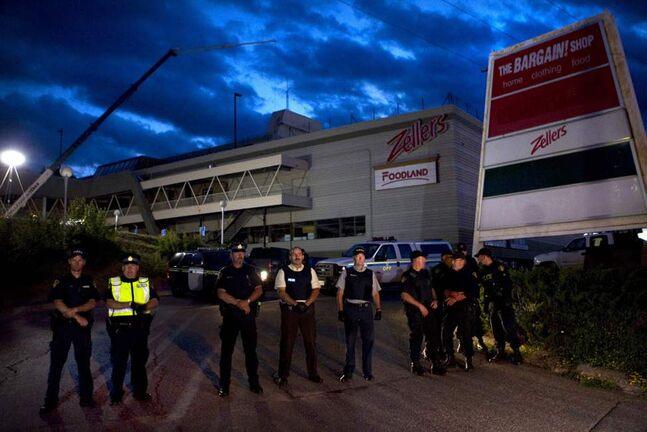 Police form a line outside the Algo Centre Mall in Elliot Lake, Ontario. According to some residents a large number of miners are due to arrive from Timmins to join a locally planned rescue effort. Officials in Elliot Lake, Ont., say they are resuming rescue efforts at a partially collapsed mall after an appeal from Ontario Premier Dalton McGuinty. (The Canadian Press / Chris Young)