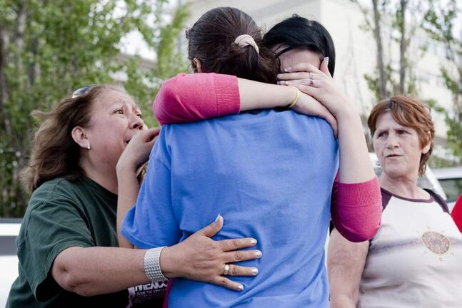 Local residents react to the news that authorities have called off a rescue bid for any survivors at the site of the collapsed roof of the Algo Centre Mall in Elliot Lake, Ontario, as the site is deemed too dangerous. (The Canadian Press / Chris Young)