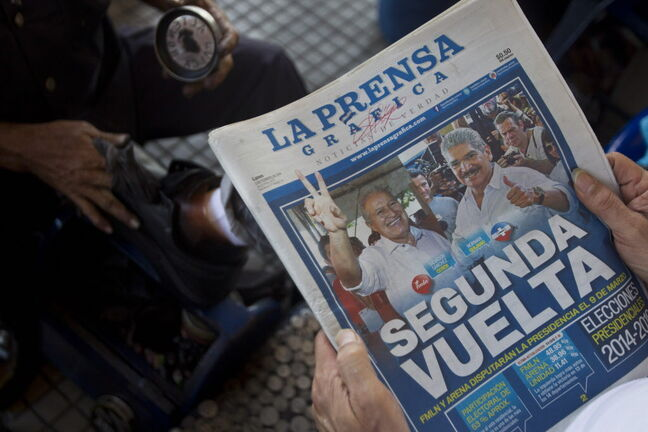 A man reads a newspaper with the elections results as front page news, with a headline that reads in Spanish,