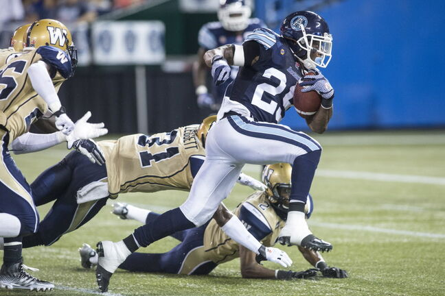 Toronto Argonauts Curtis Steele breaks through the Winnipeg Blue Bombers defence to score his team's first touch down during the first half of the game in Toronto on Tuesday.