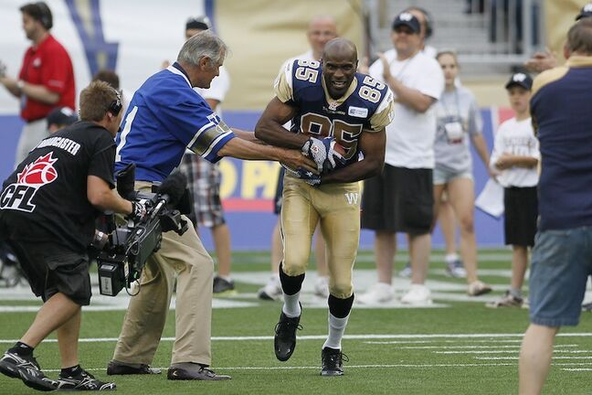 Former Winnipeg Blue Bomber Milt Stegall gets the handoff from Ken Ploen in the pre-game ceremony.