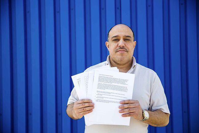 Food Fare owner Munther Zeid poses for a portrait with his petition to change the provincial act on store opening hours at Food Fare in Winnipeg on Friday.