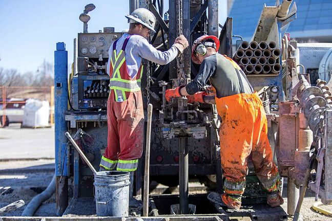 Adam Zurbyk (left) and Dylan Goertzen drill boreholes at The Forks Wednesday in preparation for what will become a district geothermal energy system at the Railside at The Forks development.