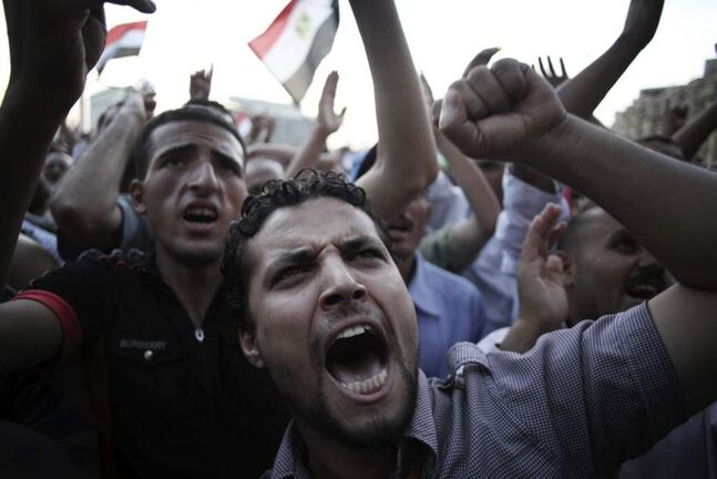 Egyptian men chant anti-Supreme Council for the Armed Forces (SCAF) slogans in Tahrir Square in Cairo, Egypt. Authorities delayed Thursday's planned announcement of the winner of Egypt's presidential election. (AP Photo/Manu Brabo)
