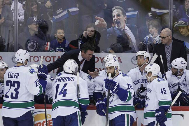 Winnipeg Jets fans taunt the Vancouver Canucks bench with an image of their head coach John Tortorella during a break in play in the first period NHL action in Winnipeg on Friday, January 31, 2014. Tortorella is sitting out a six-game suspension.