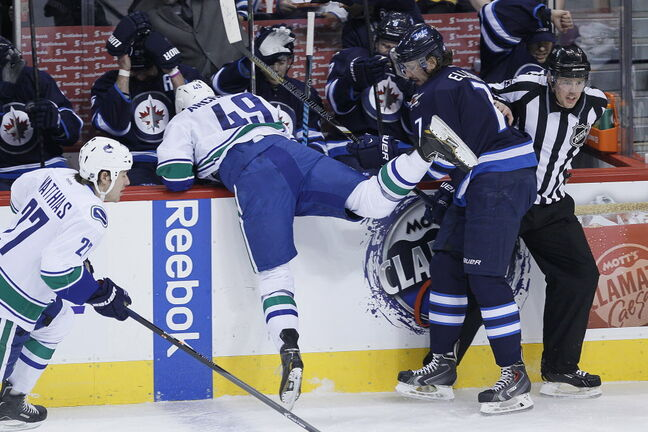 Vancouver Canucks' Darren Archibald (49) gets checked into the Winnipeg Jets bench by Jets' Keaton Ellerby (7) during the first period.