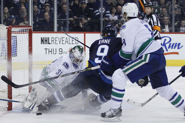 Vancouver Canucks' Christopher Tanev (8) gets called for a penalty shot on Winnipeg Jets' Evander Kane (9) in front of goaltender Eddie Lack (31) during the second period.