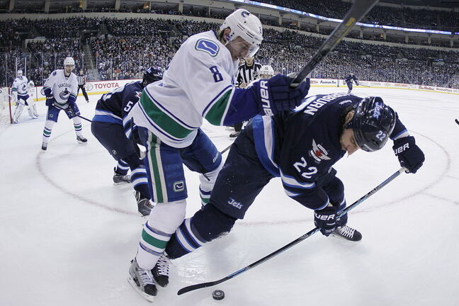 Winnipeg Jets' Chris Thorburn (22) and Vancouver Canucks' Christopher Tanev (8) fight for the puck in the Canucks corner during second period NHL action in Winnipeg.