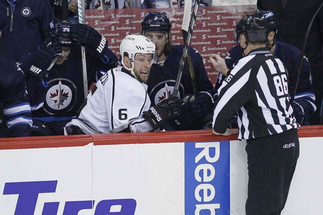 Los Angeles Kings' Jake Muzzin (6) climbs out of the Winnipeg Jets' bench after being dumped over the boards.