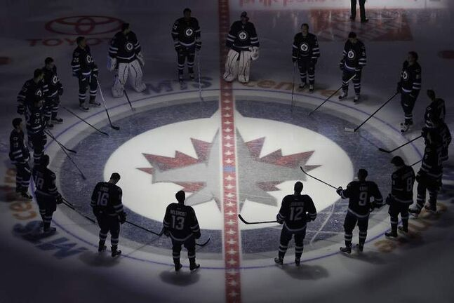 The Winnipeg Jets gather at centre ice prior to their game with the Ottawa Senators in Winnipeg Saturday
