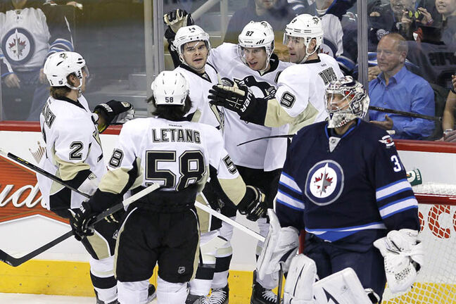 Penguins' Sidney Crosby, 87, Chris Kunitz, 14, Pascal Dupuis, 9, Matt Niskanen, 2, and Kris Letang, 58, celebrate Crosby's first goal against the Winnipeg Jets, Friday night. It was Crosby's first of two goals in his first NHL game at MTS Centre.