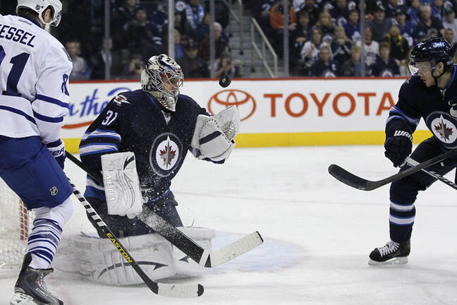 Winnipeg Jets goaltender Ondrej Pavelec reaches for the puck as Tobias Enstrom and Toronto Maple Leafs' Phil Kessel look for the rebound during the second period in Winnipeg on Thursday.