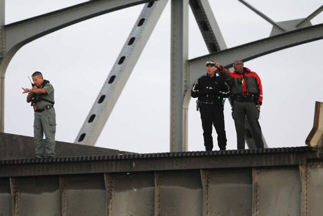 Rescue workers look over the edge where a portion of the Interstate 5 bridge collapsed into the Skagit River.