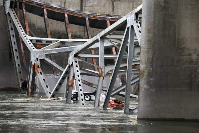 A car, lower right, and what is believed to be a travel trailer lie in the Skagit River with debris from the collapsed portion of the Interstate 5 bridge on  Friday in Mount Vernon, Wash. A truck carrying an oversize load struck the four-lane bridge on the major thoroughfare between Seattle and Canada, sending a section of the span and two vehicles into the Skagit River below Thursday evening. All three occupants suffered only minor injuries. At an overnight news conference, Washington State Patrol Chief John Batiste blamed the collapse on a tractor-trailer carrying a tall load that hit an upper part of the span.
