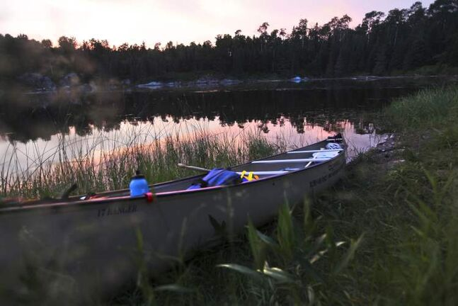 The canoe sits along the edge of reeds near Charles' hunting cabin, located roughly halfway through the journey.
