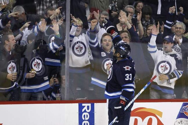 Winnipeg Jets defenceman Dustin Byfuglien salutes the fans after scoring against the Florida Panthers during second-period NHL action in Winnipeg Thursday,.