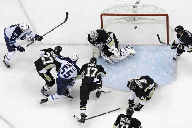 Jets forward Evander Kane (left) fires a backhand shot past Penguins goalie Marc-Andre Fleury for his second goal of the second period as teammate Mark Scheifele draws a crowd of Penguins to the crease.