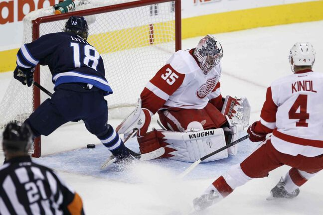 Winnipeg Jets forward Bryan Little (18) scores on a breakaway against Detroit Red Wings goaltender Jimmy Howard as Wings defenceman Jakub Kindl tries to catch up.