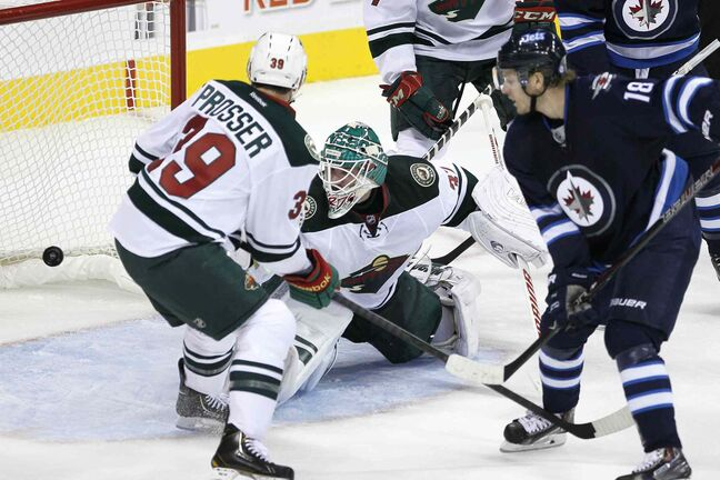 Bryan Little scores on Minnesota Wild goaltender Josh Harding as the Wild's Nate Prosser looks on during the first period.