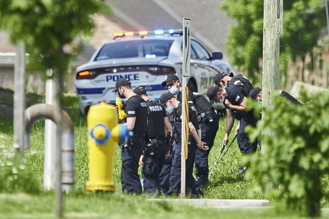 A line of police officers look for evidence at the scene of a car crash in London, Ontario on Monday, June 7, 2021. THE CANADIAN PRESS/Geoff Robins