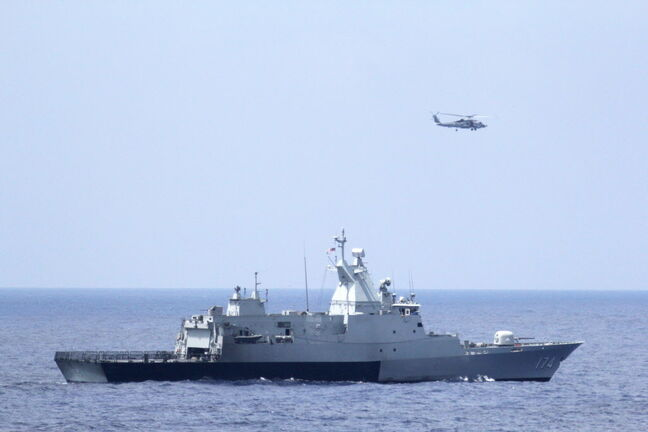 This photo provided by the U.S. Navy shows the Royal Malaysian Navy corvette KD Terengganu and a U.S. Navy MH-60R Sea Hawk helicopter conduct a coordinated air and sea search for a missing Malaysian Airlines jet in the Gulf of Thailand.